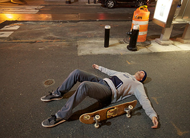 Scott lying on the ground next to his skateboard