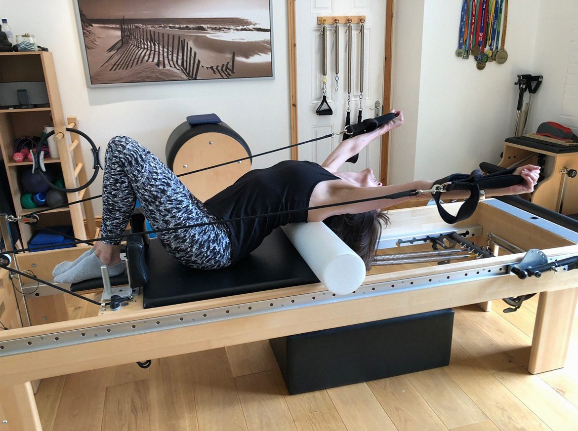 Woman using a roller on a reformer